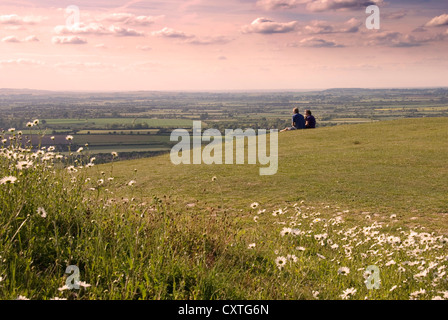 Bucks - Chiltern Hills - on Whiteleaf Hill - late afternoon light - couple seated on the grass - enjoying the view - Stock Photo