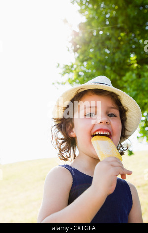 Girl eating popsicle outdoors - Stock Photo