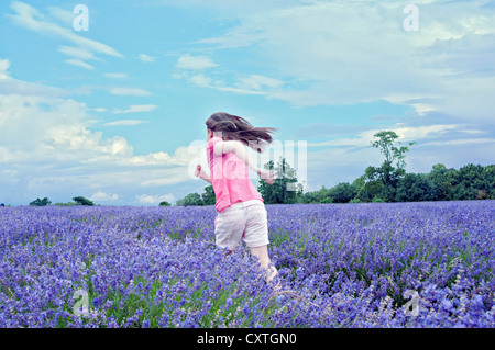 Girl running in field of flowers - Stock Photo