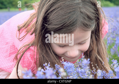 Close up of girl smelling flowers - Stock Photo