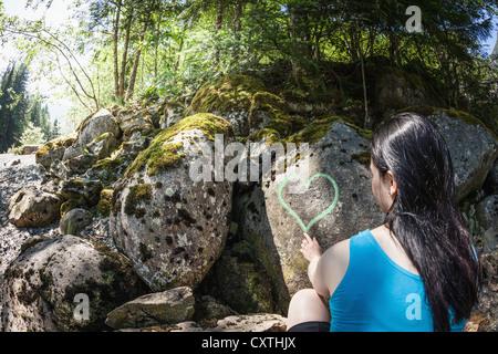 Woman drawing heart on rocks - Stock Photo