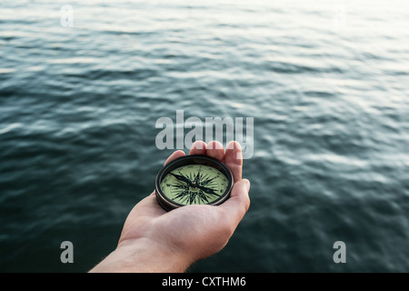 Close up of hand holding compass - Stock Photo