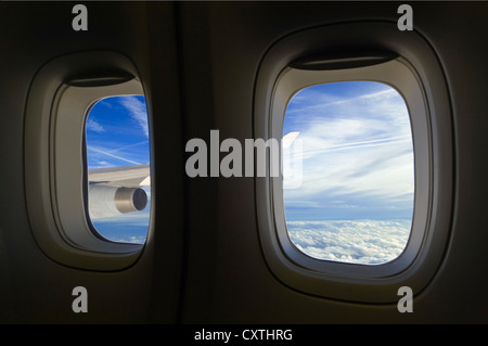 Horizontal view through an aeroplane window of cumulus and stratocumulus clouds and vapour trails across the sky. - Stock Photo