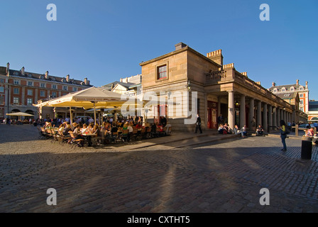 Horizontal wide angle of people enjoying a leisurely drink in the evening sun at one of the street cafes in Covent - Stock Photo