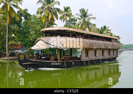 Horizontal view of a huge traditional wooden house boat, kettuvallam, sailing through the backwaters of Kerala. - Stock Photo