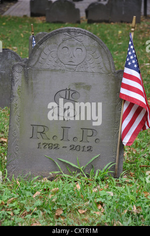 Old grave with US dollar $ 1792 - 2012 and R.I.P. engraved on tombstone - Stock Photo