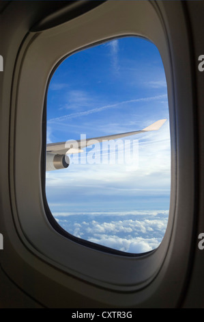 Vertical view through an aeroplane window of cumulus and stratocumulus clouds and vapour trails across the sky. - Stock Photo