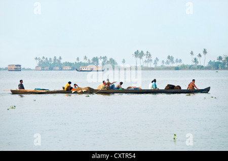 Horizontal view of workers returning home at the end of the day in traditional canoes in the backwaters of Kerala. - Stock Photo
