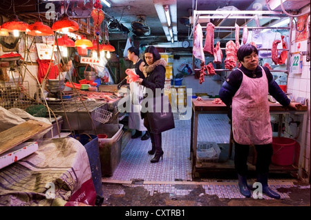 A Chinese woman in fashionable clothes and carrying a shopping bag from an upscale retailer prepares to to leave - Stock Photo
