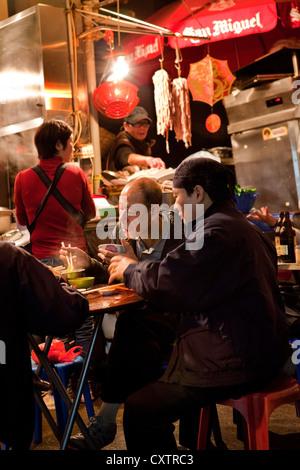 A table of men enjoy dinner at a street restaurant in Hong Kong's Central Market. - Stock Photo