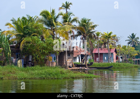 Horizontal wide angle of small traditional homes along the riverbank in the backwaters of Kerala - Stock Photo