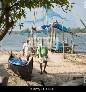 Square portrait of two Indian fishermen near the Chinese fishing nets in Fort Cochin. - Stock Photo