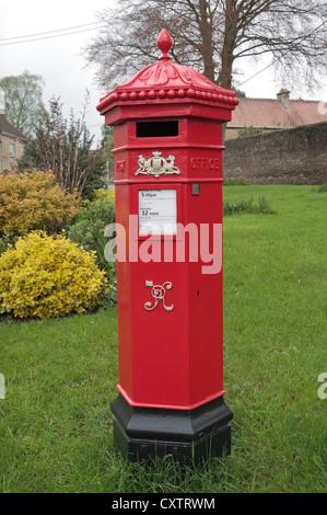 An original bright red Victorian Royal Mail Penfold pillar box (post box) in Tetbury, Gloucestershire, UK - Stock Photo