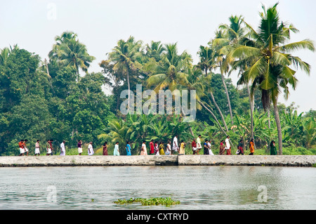 Horizontal view of a line of Indian people walking along the riverbank in Kerala. - Stock Photo