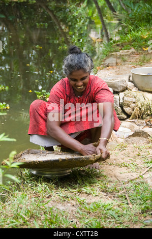 Vertical portrait of an Indian woman waterproofing a handmade grass basket with mud on the riverbank in Kerala.