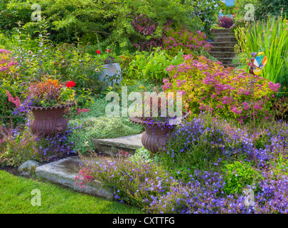 Vashon Island, WA: Potted urns on the entrance of stone stairway with summer perennial garden - Stock Photo