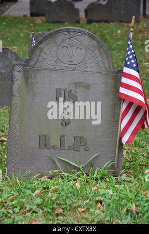 Old grave with US dollar $ and R.I.P. engraved on tombstone - Stock Photo