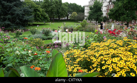 People relaxing in the Inner Temple Garden by the flower beds with yellow flowers and canna plants in summer in - Stock Photo