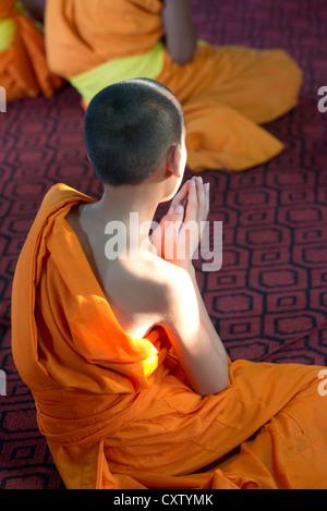 A young monk sits in prayer in the meditation hall of Wat Xieng Thong. Luang Prabang, Laos - Stock Photo