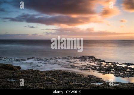 Incoming tide at sunrise, Robin Hood's Bay, North Yorkshire, England, UK, long exposure - Stock Photo