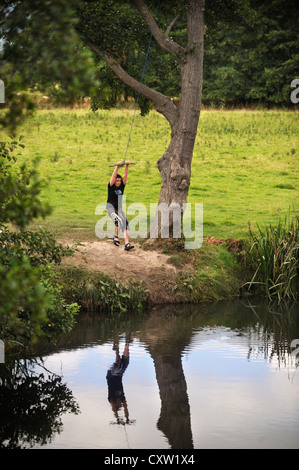 A boy playing on a rope swing over the River Teme near the village of Leintwardine, Herefordshire UK - Stock Photo
