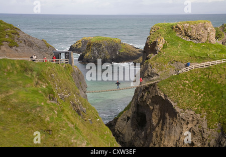 Ballintoy Co Antrim Northern Ireland Visitors crossing the popular Carrick-a-Rede rope bridge to the island - Stock Photo