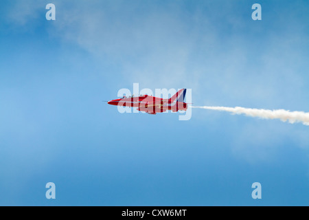 Red Arrows plane with smoke against blue sky, WESTON-SUPER-MARE, SOMERSET-JULY 23RD 2012: - Stock Photo
