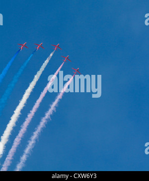Red Arrows jets pink white blue smoke against vibrant blue sky - Stock Photo