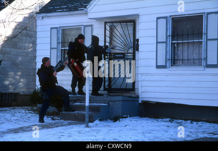 Narc officers from Detroit Police Department Narcotics unit, force entry into a suspected drug address. - Stock Photo