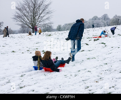 Enjoying the snow - Man pulling two children on sleds in snowy Richmond Park in Winter,Richmond upon Thames,Greater - Stock Photo