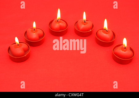 Background of red silk drape and six flaming candles - Stock Photo