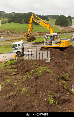 Man excavating soil for new home on steep sloping section, surrounded by rural views. - Stock Photo