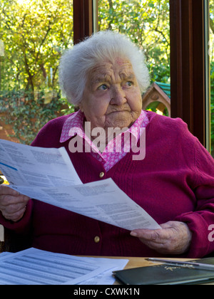 BILLS STATEMENTS ELDERLY WORRY Concerned elderly senior lady at home reading and  contemplating her latest financial statements and bills Stock Photo