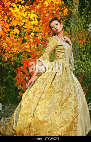 A pretty young woman in her late teens or early 20s in a beautiful fancy dress with colorful autumn trees - Stock Photo