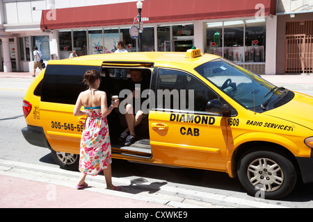 couple getting into minivan yellow cab taxi with coffees in miami south beach florida usa - Stock Photo