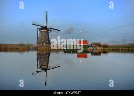 A typical Dutch windmill at Kinderdijk is reflected in a canal in the evening light as the moon rises - Stock Photo