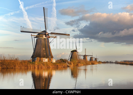 Five typical Dutch windmills at Kinderdijk stretch into the distance along a canal where they are reflected in the - Stock Photo