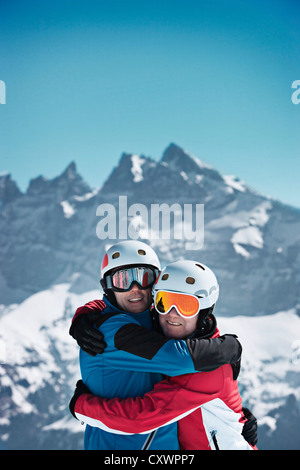 Skiers hugging on snowy mountain - Stock Photo