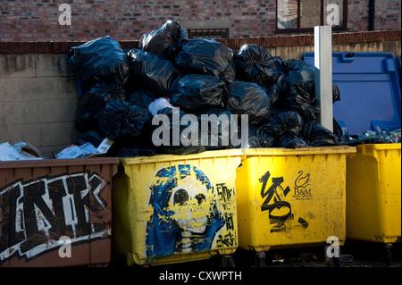 Rubbish bins black sacks piled high overflowing refuse - Stock Photo