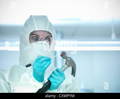 Forensic student examining bloody hammer - Stock Photo
