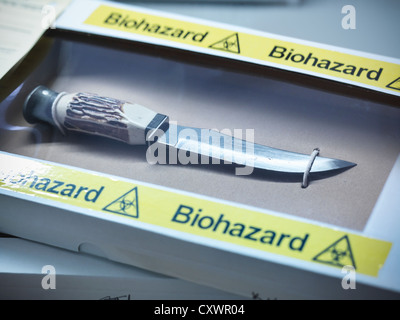 Knife in forensic biohazard box - Stock Photo