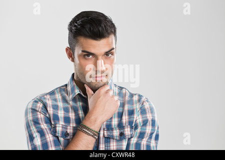 Man holding chin in hands - Stock Photo
