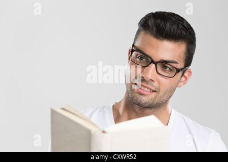 Smiling man reading book - Stock Photo