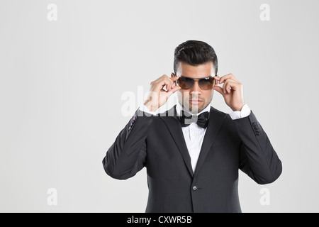 Man in tuxedo adjusting his sunglasses - Stock Photo
