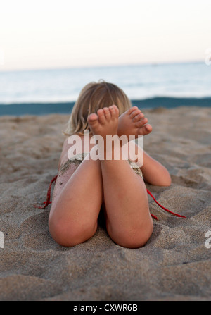 Toddler laying on beach - Stock Photo