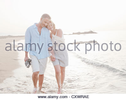 Couple walking in waves on beach - Stock Photo