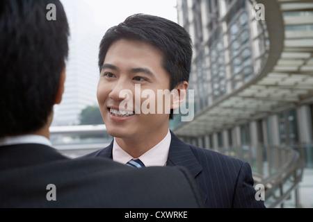 Businessmen talking on walkway - Stock Photo