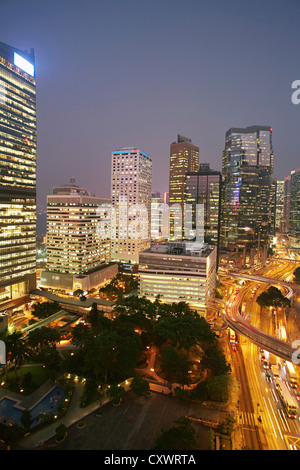 Urban skyscrapers lit up at night - Stock Photo