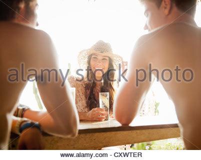 Friends having drinks outdoors - Stock Photo