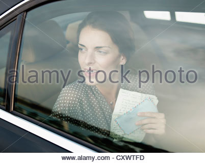 Woman holding letter in backseat of car - Stock Photo